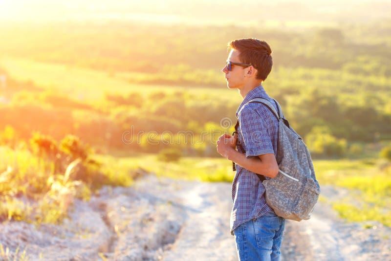 站立在有看太阳的背包的路的一个年轻人 库存照片
