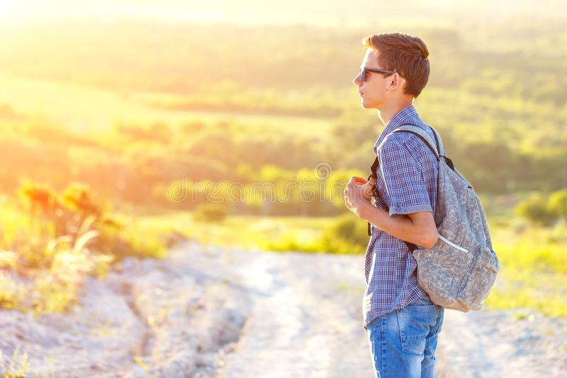 站立在有看太阳的背包的路的一个年轻人 免版税库存照片