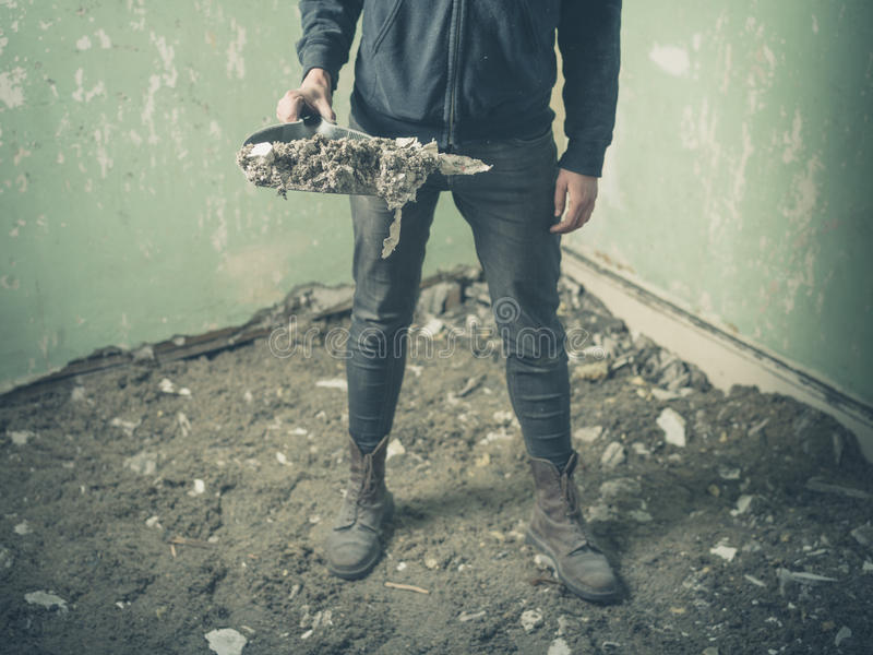 站立在有簸箕的遗弃屋子里的人 免版税图库摄影