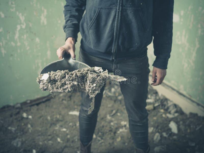 站立在有簸箕的遗弃屋子里的人 库存图片