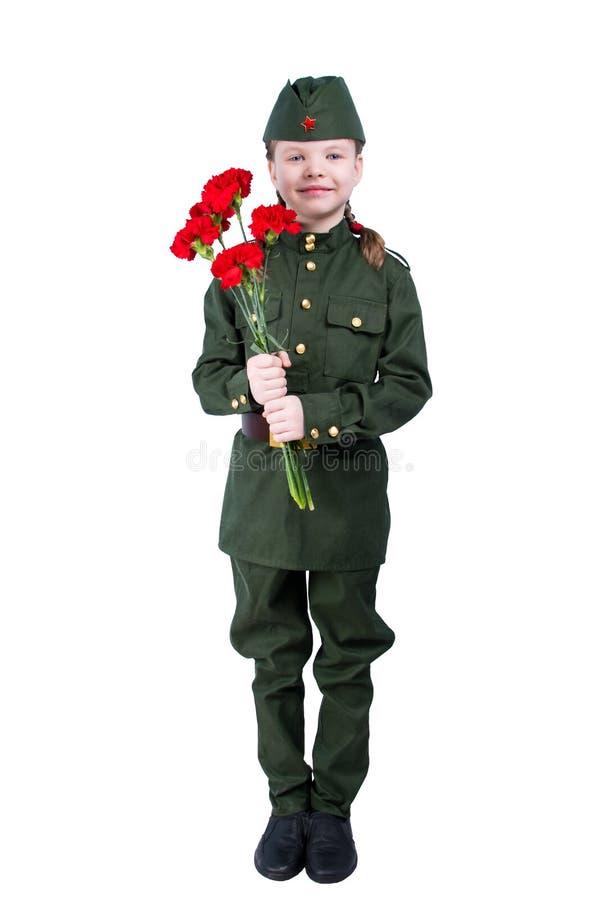 站立在有红色花的制服的女婴,在白色背景 免版税库存图片