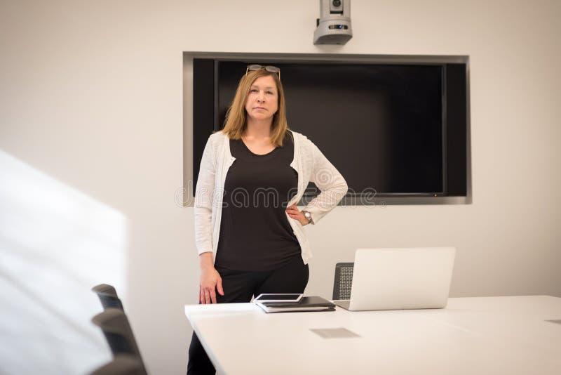 站立在有膝上型计算机的会议室的确信的女实业家 免版税库存图片