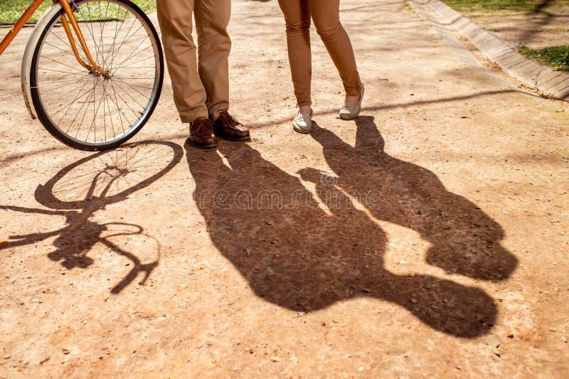 站立在有自行车和a的公园胡同的夫妇的阴影 库存图片