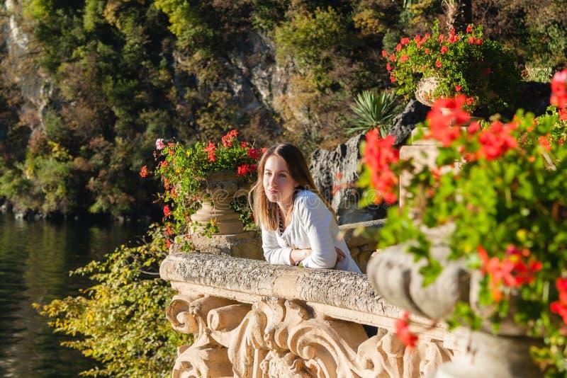 站立在有花的老大阳台阳台的女孩 免版税库存图片