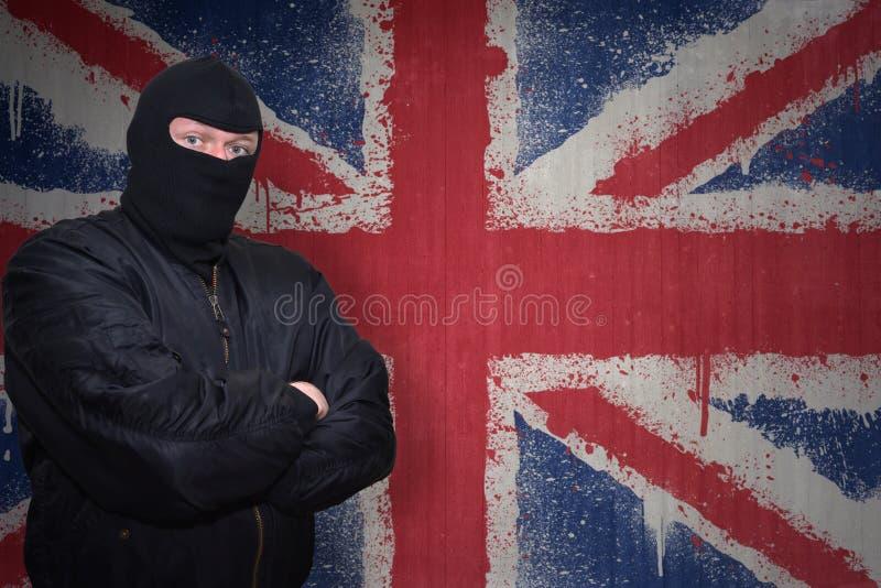 Download 站立在有英国的被绘的国旗的墙壁附近的面具的人 库存照片. 图片 包括有 恶霸, 犯罪, 扶手, 王国, 罪行 - 72354468