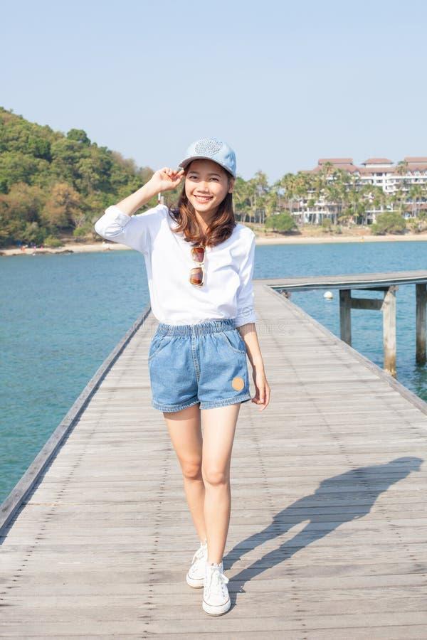 站立在有蓝色海水的木码头的年轻美丽的妇女 库存照片
