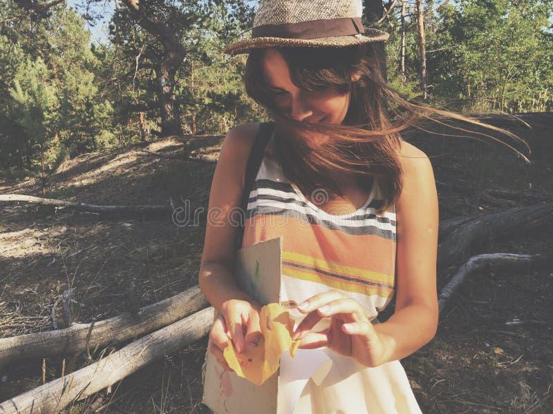 站立在有西部帽子的顶面礼服的少妇在森林前面的高草 免版税库存图片