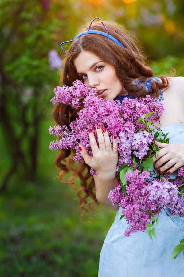 站立在有锂分支的庭院里的美丽的少妇  免版税库存照片