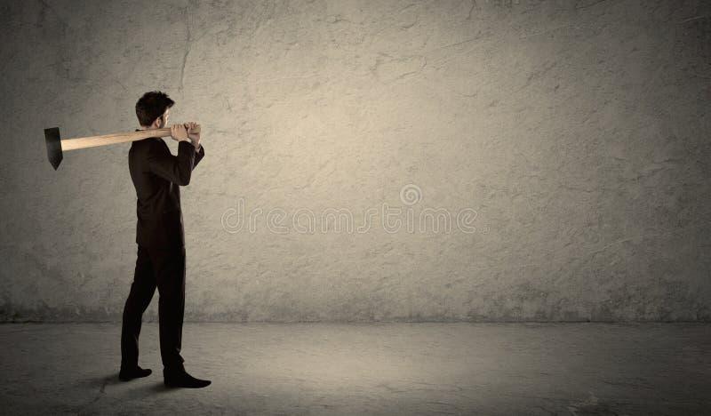 站立在有锤子的脏的墙壁前面的商人 免版税库存照片