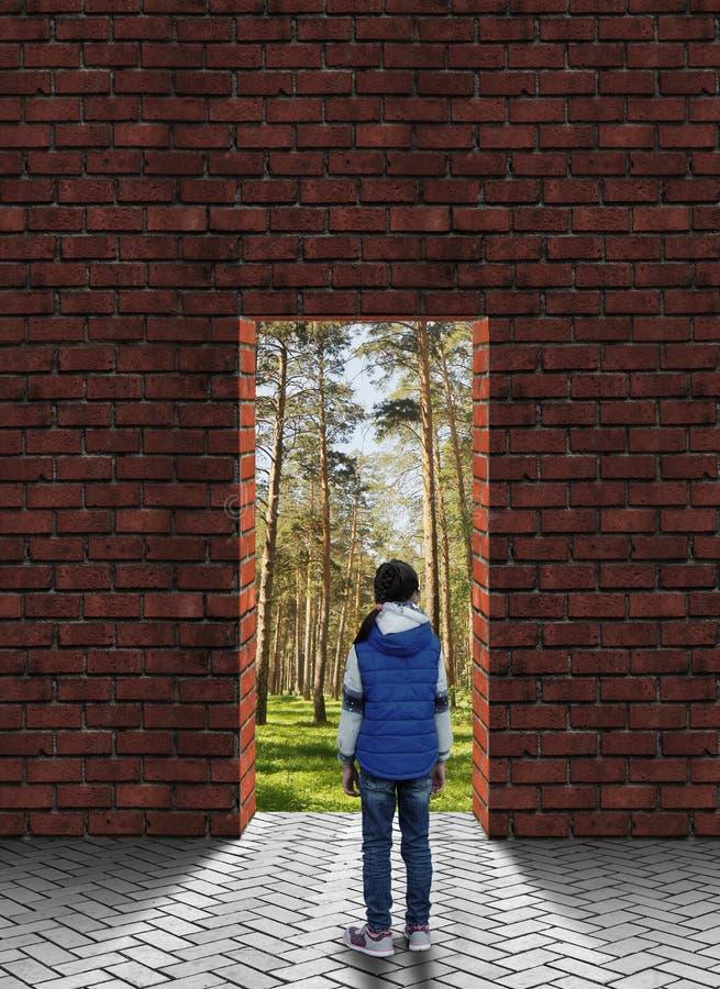 站立在有门道入口的墙壁前面的小女孩被一个美丽的杉木森林跟随了 免版税库存照片