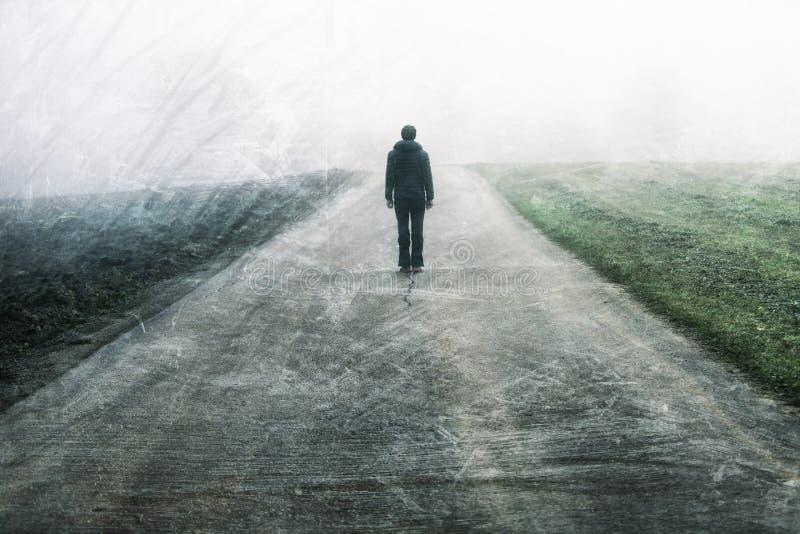 站立在有雾的路的男性收养 库存照片
