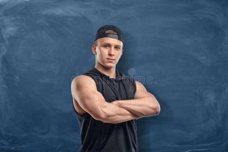 站立在有他的胳膊的一个空的黑板前面的年轻大力士 免版税库存图片