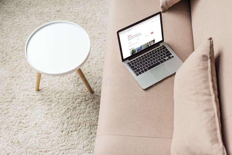 站立在有airbnb网站的舒适长沙发的膝上型计算机大角度看法 免版税库存图片