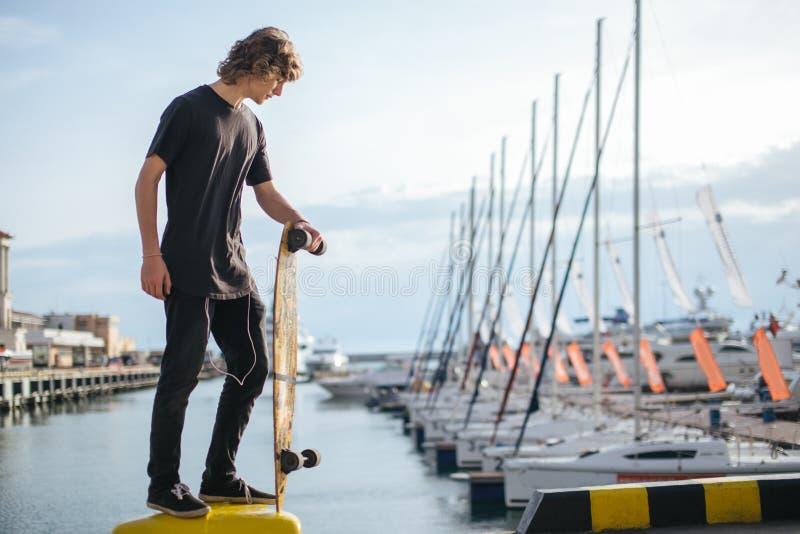 站立在有longboard的码头和看游艇的卷曲人 库存照片