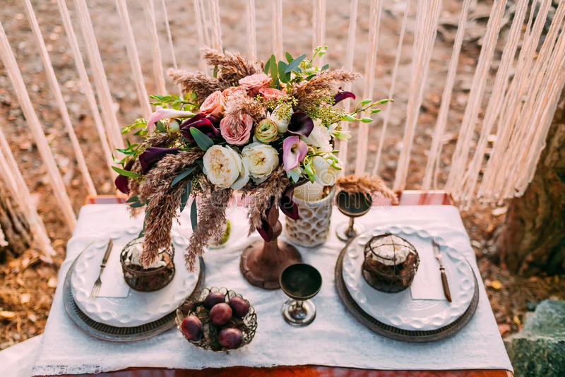 站立在服务的桌上的不同的花的构成在婚礼聚会区域  植物布置 免版税图库摄影