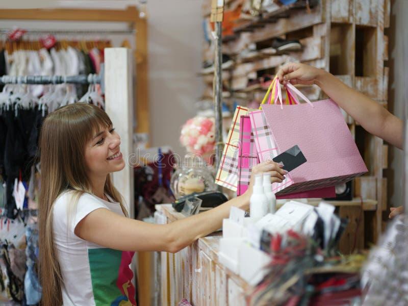 站立在服装店和支付她的购买的一名满意的妇女 一shopaholic在被弄脏的背景 库存照片