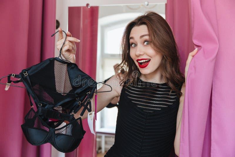 站立在服装店的妇女户内拿着女用贴身内衣裤 图库摄影