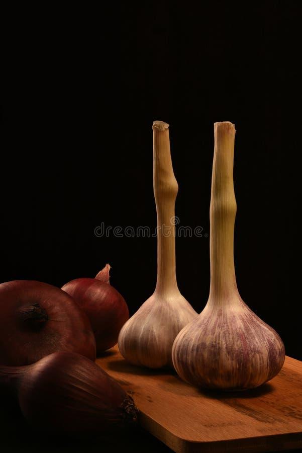 站立在木切板en的新鲜的大蒜两个头反对黑背景 有红洋葱3个头  库存图片