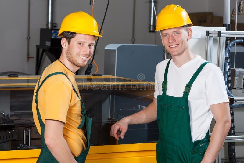 站立在机器旁边的工作者 免版税库存图片
