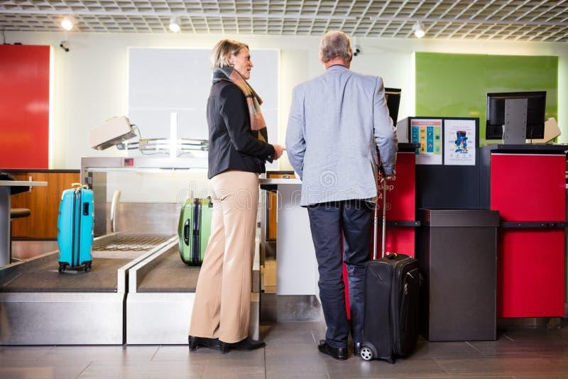 站立在机场报道登记柜台的资深企业夫妇 库存照片