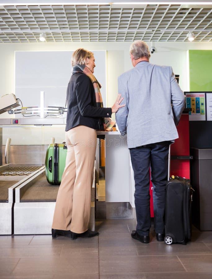 站立在机场报道登记柜台的资深企业夫妇 库存图片