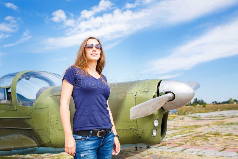 欧美少妇飞机_站立在机场的少妇近的体育飞机. 学校, 如同.