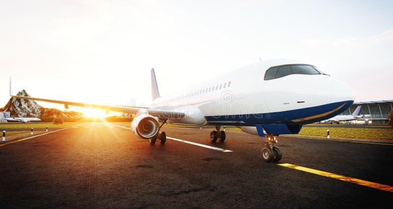 站立在机场跑道的白色商业飞机在日落 乘客飞机正面图离开 免版税库存照片