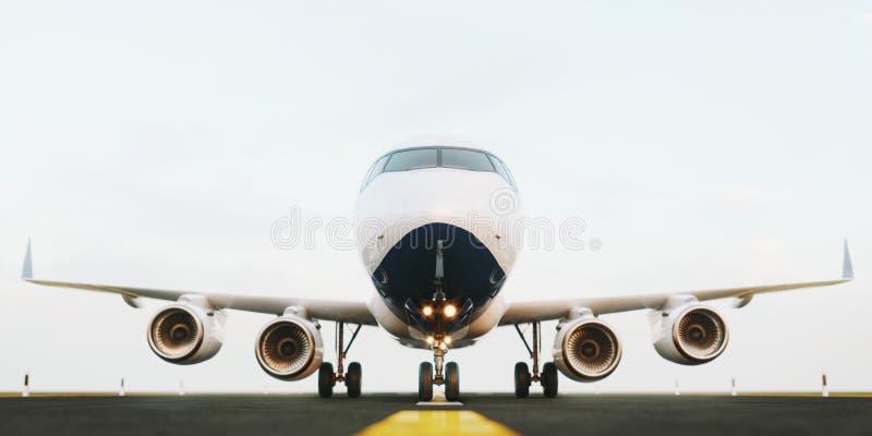 站立在机场跑道的白色商业飞机在日落 乘客飞机正面图离开 免版税图库摄影