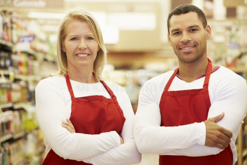 站立在杂货走道的超级市场工作者 库存照片