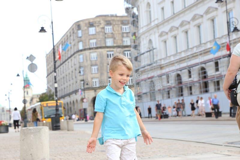 站立在杆的一个小白肤金发的男孩 免版税库存图片