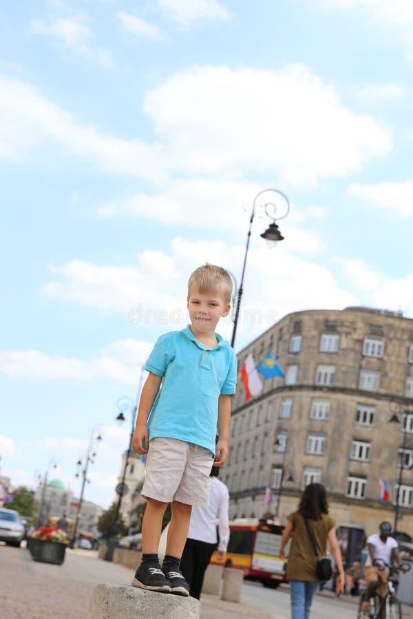 站立在杆的一个小白肤金发的男孩 免版税图库摄影