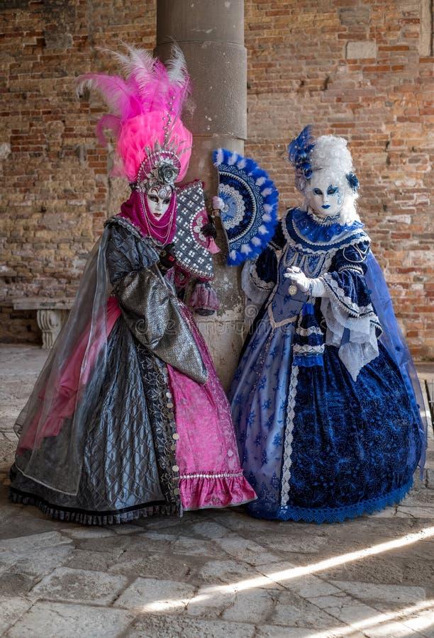 站立在柱子旁边的华丽蓝色和桃红色服装的被掩没的妇女在威尼斯狂欢节期间 库存照片