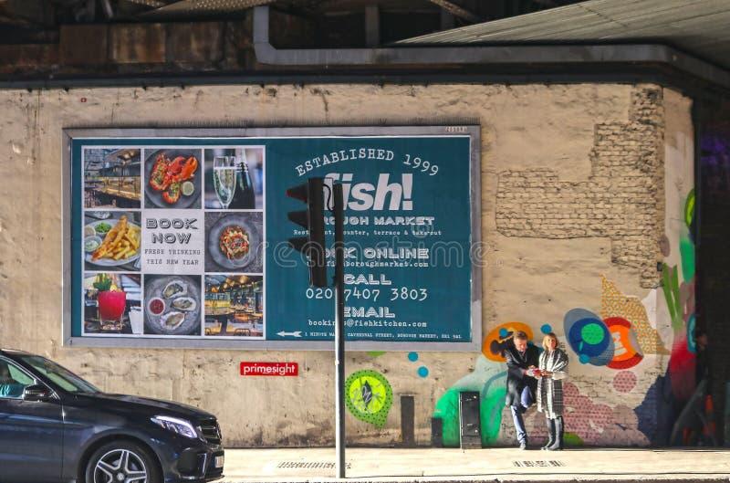 站立在标志前面的边路的夫妇给鱼做广告在与艺术的自治市镇市场上在他们后的墙壁上 免版税库存图片