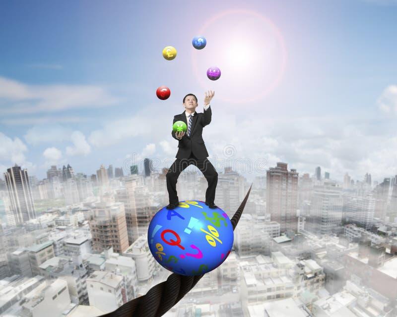 站立在标志球的玩杂耍的商人平衡在导线 免版税图库摄影