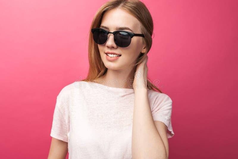 站立在桃红色背景佩带的牛仔裤的玻璃的美丽的年轻白肤金发的女孩,桃红色上面微笑的雪白微笑,佩带的黑色 免版税库存照片