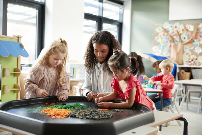 站立在桌上的两位年轻女小学生打与他们的女老师的一场比赛在一间幼儿学校教室,选择聚焦 免版税图库摄影
