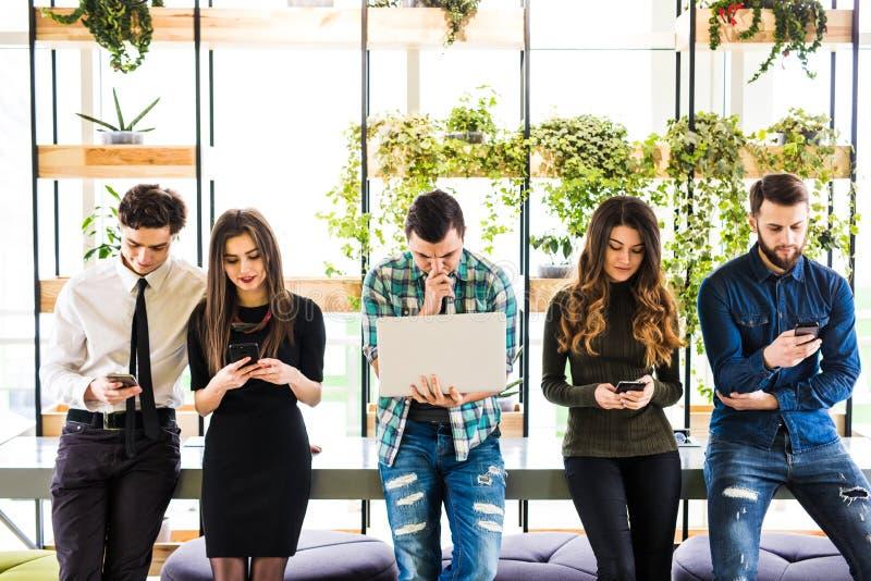 站立在桌上的小组朋友和大家在现代办公室室使用他的divices 同时在设备的乐趣 库存图片