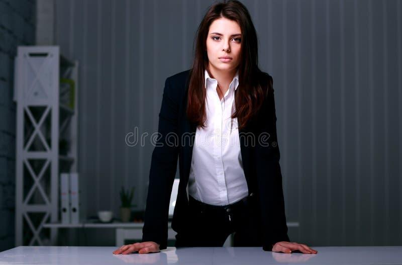 站立在桌附近的年轻美丽的女实业家 库存照片