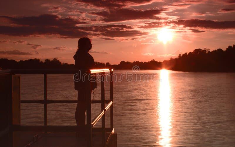 站立在桥梁的妇女在湖在日落 库存照片