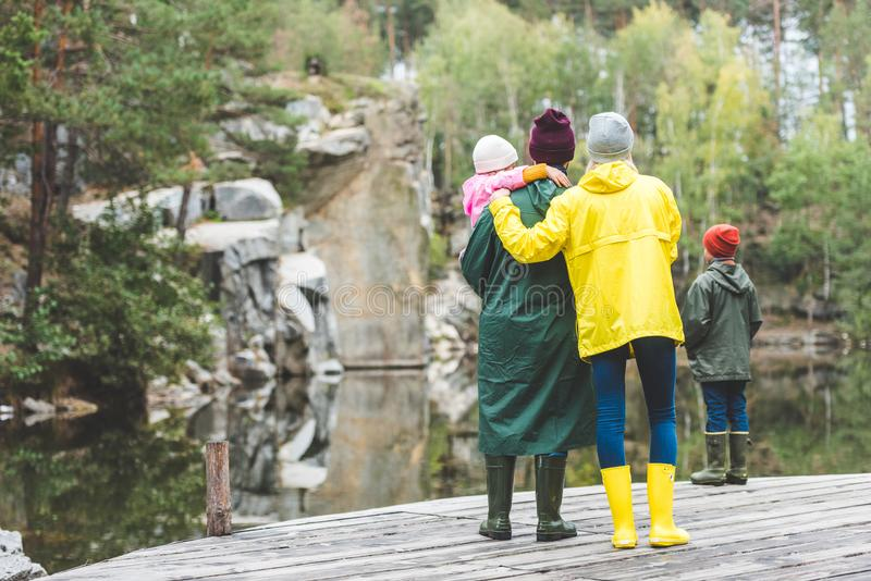 站立在桥梁的家庭在秋天森林里 免版税库存图片