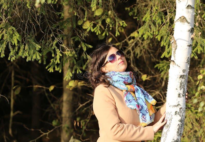 站立在桦树附近的女孩 免版税图库摄影