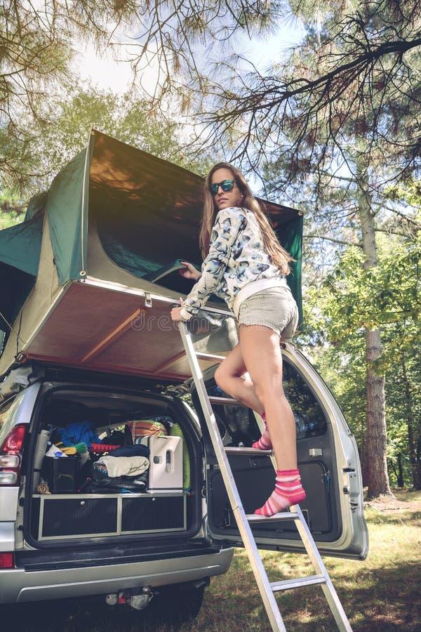 站立在梯子在汽车的开头帐篷的妇女 免版税库存照片