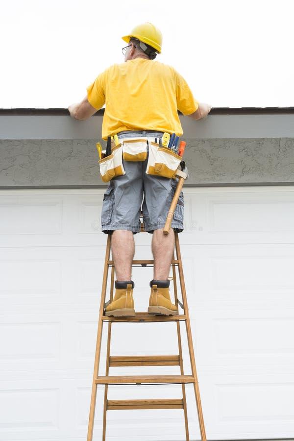 站立在梯子的承包商 免版税库存照片