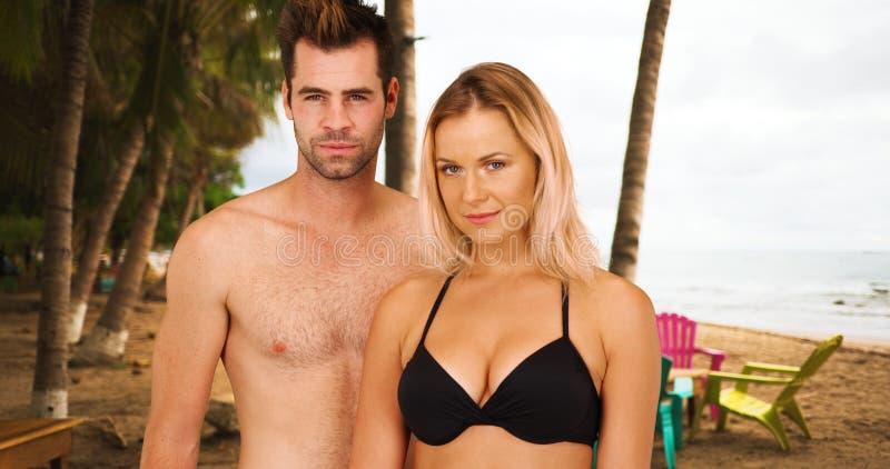 站立在棕榈树下的性感的白色千福年的夫妇画象在海滩 免版税库存照片