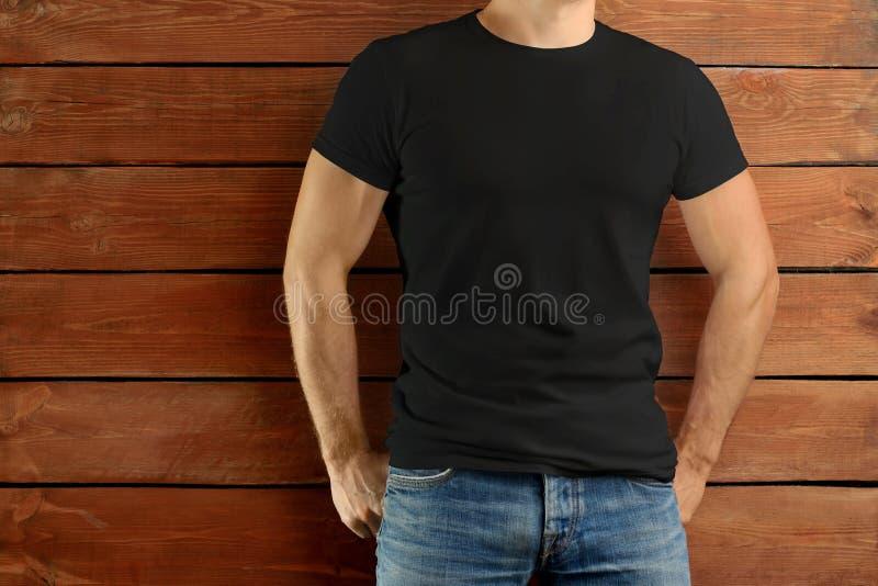 站立在棕色木演播室背景的一件黑T恤杉和蓝色牛仔裤的运动适合的人 免版税图库摄影