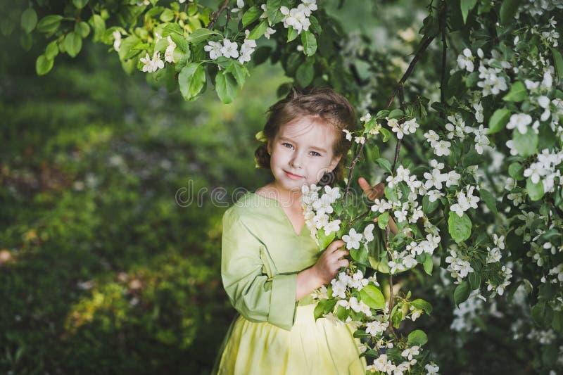 站立在樱桃blo的分支的附近孩子的画象 免版税库存照片