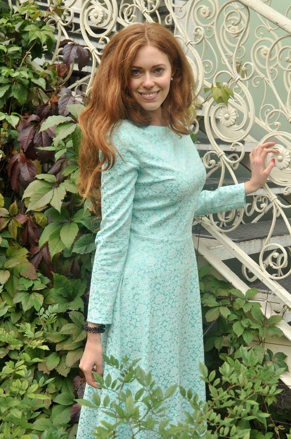 站立在步行微笑的礼服的美丽的红发女孩 免版税库存图片