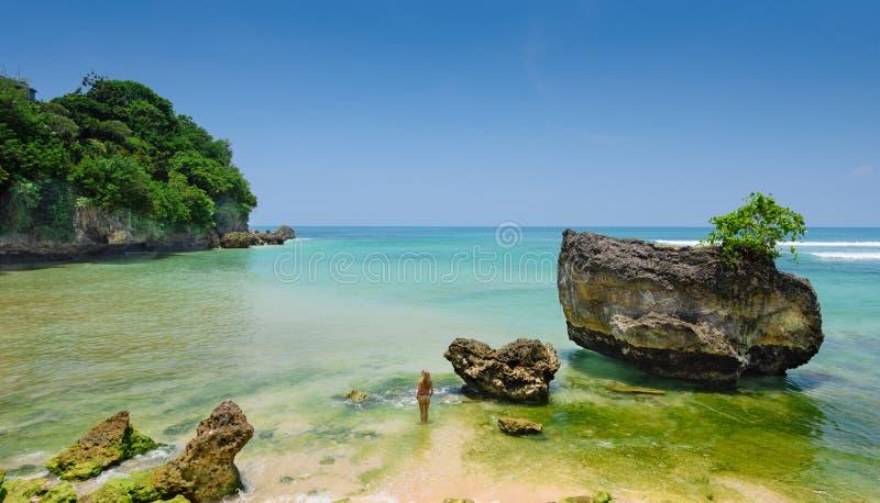 站立在水中的宽银幕观点的女孩在padang padang海滩在巴厘岛 免版税库存图片