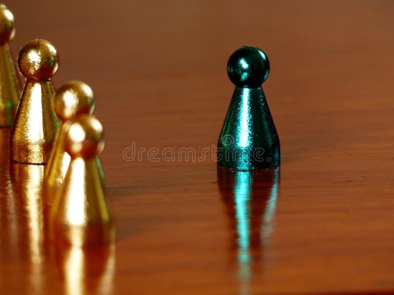 站立在水平一张木的桌上的金黄象征前面的一个金属绿色象征 免版税图库摄影