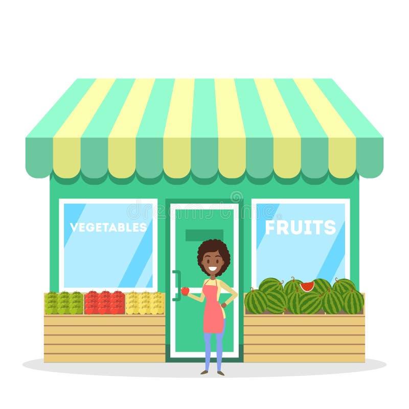 站立在水果和蔬菜商店前面的女性卖主 皇族释放例证
